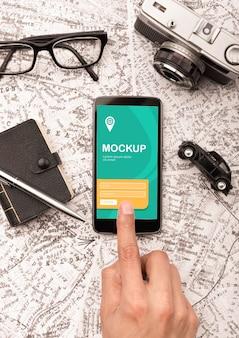Vista superior do smartphone com óculos e carteira para viajar