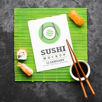 Vista superior do sushi com pauzinhos e molho de soja no rolo de bambu