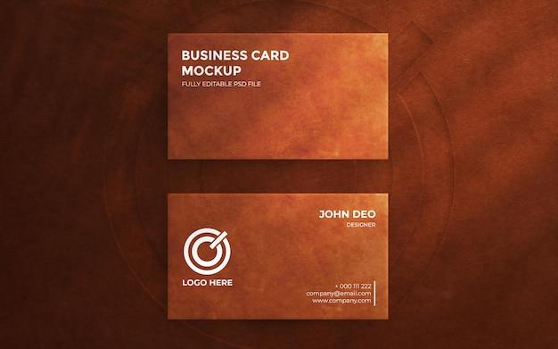 Vista superior em um cartão de visita elegante em fundo de couro com maquete de logotipo em relevo