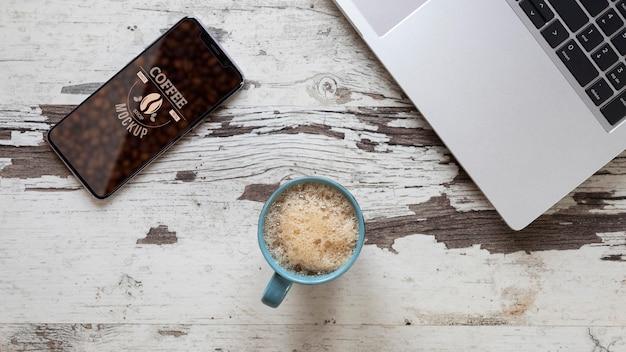 Vista superior em uma xícara de café com maquete de telefone