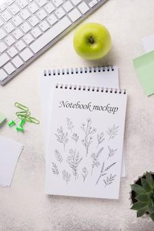 Vista superior maquete de notebook e artigos de papelaria perto de maçã e teclado
