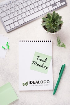 Vista superior mock-up notebook e artigos de papelaria perto de planta suculenta e teclado
