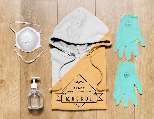 Vista superior modelo de capuz dobrado com luvas, máscara e desinfetante para as mãos