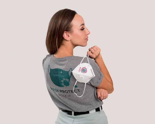 Vista traseira de mulher segurando máscara por cima do ombro Psd grátis