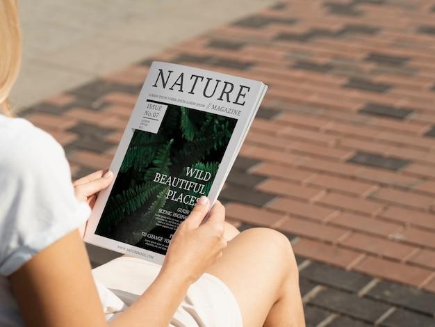Vista traseira mãos segurando natureza livro mock up