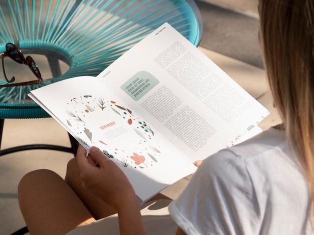 Vista traseira mulher loira olhando para um livro da natureza