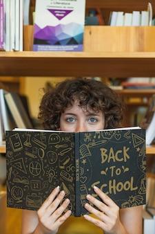 Volta ao conceito de escola com livro de leitura de menina na biblioteca