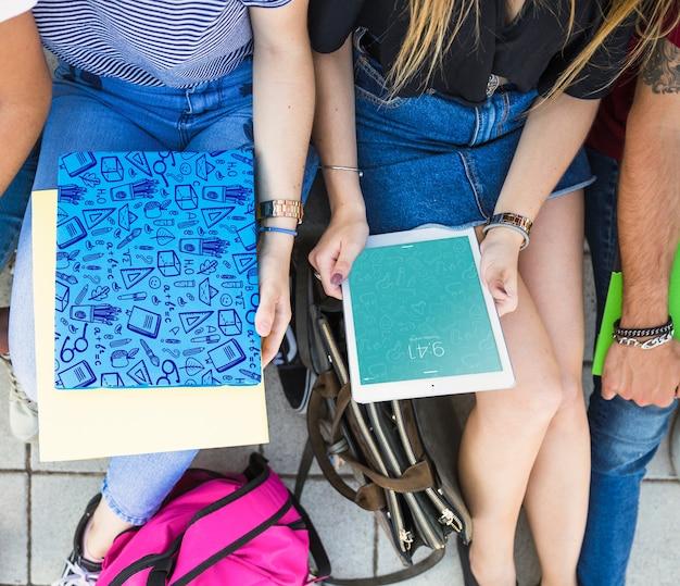 Volta ao conceito de escola com meninas olhando para tablet e capa
