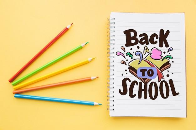 Voltar para a escola maquete com caderno e quatro lápis