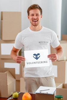 Voluntário sorridente segurando um papel em branco com caixas de comida para doação