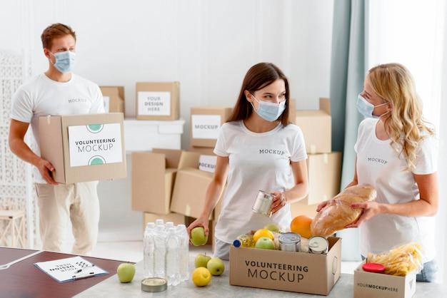 Voluntários com máscaras médicas preparando caixas de provisões para doação
