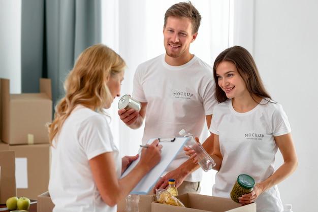 Voluntários preparando caixas de mantimentos para doações