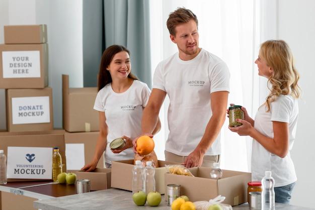 Voluntários preparando comida em caixas para doação