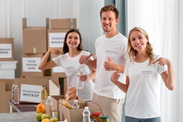 Voluntários sorridentes apontando para suas camisetas enquanto preparam comida para doação