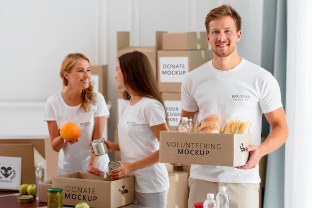 Voluntários sorridentes preparando caixas de provisões para doação
