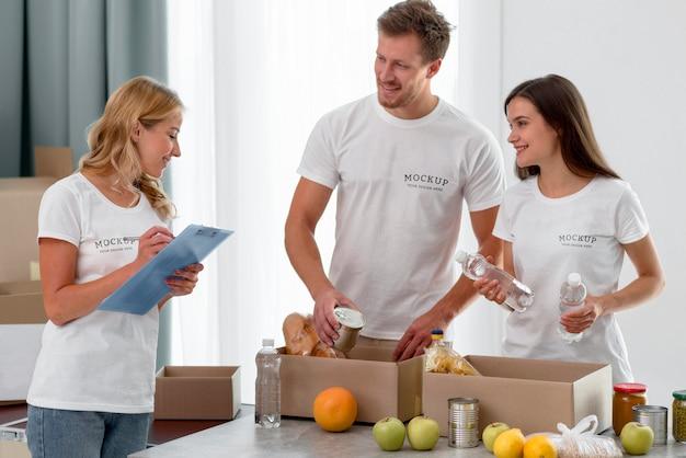 Voluntários sorridentes preparando caixas de provisões para doações