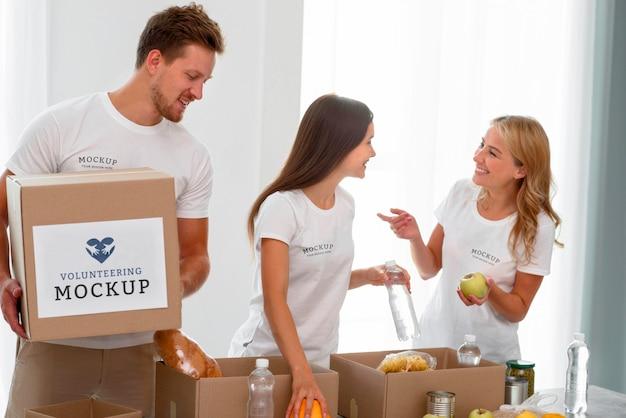 Voluntários sorridentes preparando comida para doação em caixas