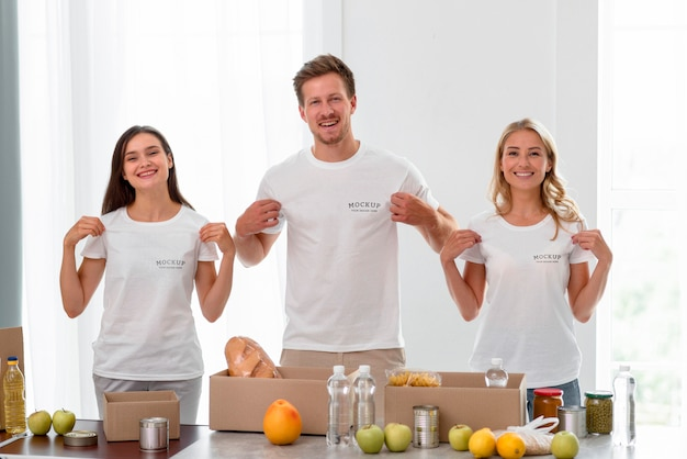 Voluntários sorridentes segurando suas camisetas enquanto preparam comida para doação