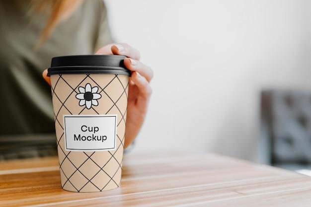 Xícara de café com maquete de mão