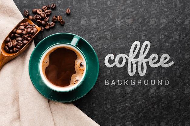 Xícara de café e colher de pau com fundo de grãos de café
