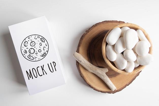 Zombar de caixa branca e tigela com seixo branco e palitos de madeira rústicos na mesa branca