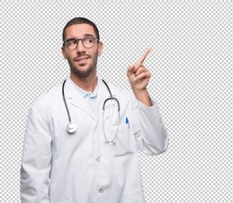 Douteux jeune docteur pointant vers le haut
