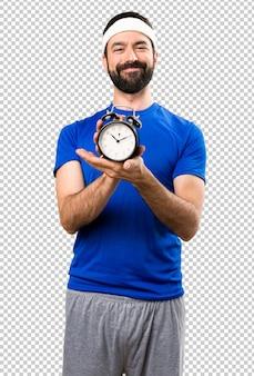 Heureux sportif drôle tenant une horloge vintage