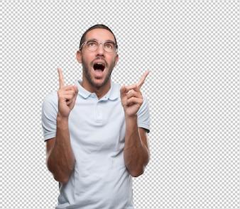 Jeune homme surpris pointant vers le haut avec ses doigts