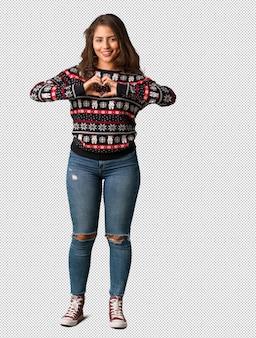 Tout le corps jeune femme portant un maillot de Noël faisant une forme de coeur avec les mains