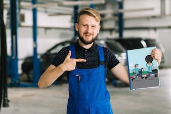 Automechaniker, der Abdeckungsmodell hält