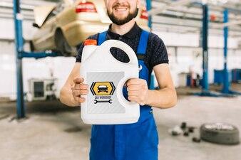 Automechaniker, der Plastikdosenmodell halten kann