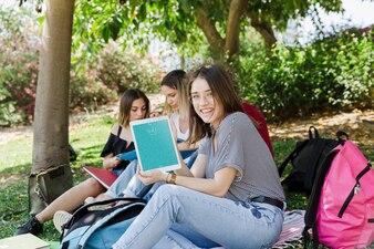 Frauen, die Tablettenmodell im Park betrachten