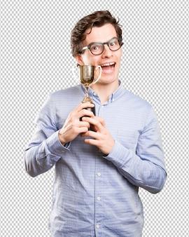 Glücklicher Sieger Kerl hält eine goldene Tasse