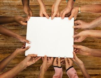 Gruppe Verschiedenartigkeitshände, die leeres Papier halten