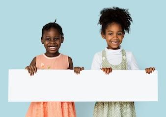 Kleines Mädchen, das leeres Suchplakat lächelt und hält
