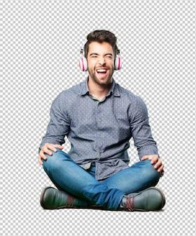 Mann, der auf dem Fußboden hört Musik sitzt