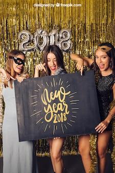 Modell des neuen Jahres mit drei Mädchen, die auf Brett zeigen