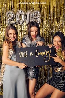 Modell des neuen Jahres mit drei Mädchen, die auf schwarzes Brett zeigen