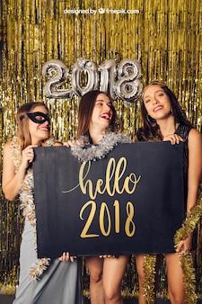 Modell des neuen Jahres mit drei Mädchen, die Brett halten