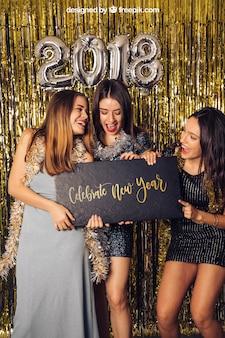 Modell des neuen Jahres mit drei Mädchen, die kleines Brett halten