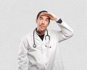 Überraschter Doktor mit Suchgeste gegen weißen Hintergrund