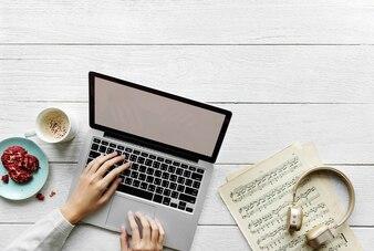 Vogelperspektive der Frau, die einen Computerlaptop auf Holztisch verwendet