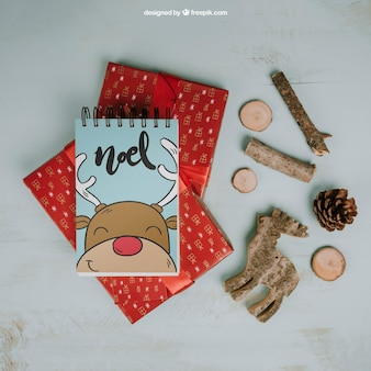Weihnachtsmodell mit Notizblock auf Geschenken