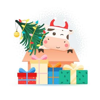 2021 année du bœuf. taureau mignon heureux en bonnet de noel assis dans une boîte en carton avec arbre de noël.