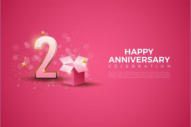 2e anniversaire avec des chiffres en or et une boîte cadeau sur fond rose.