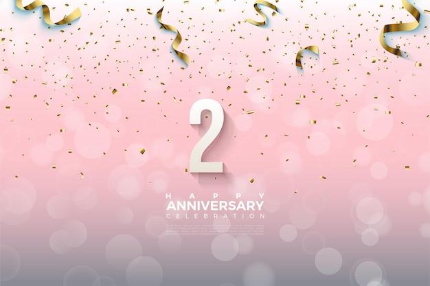 2e anniversaire avec des numéros ombrés recouverts de rubans d'or.