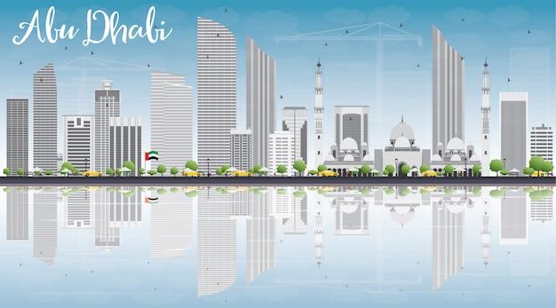 Abu dhabi city skyline avec bâtiments gris, ciel bleu et reflets.