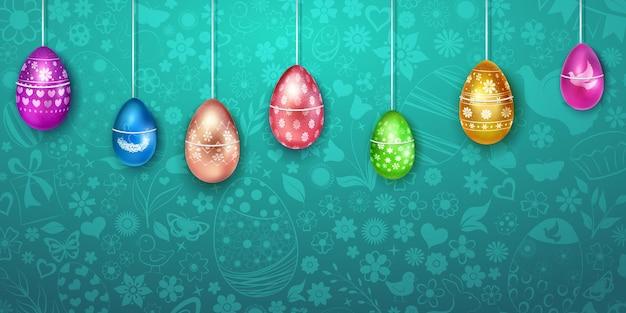 Accrocher des œufs de pâques de différentes couleurs avec une décoration colorée