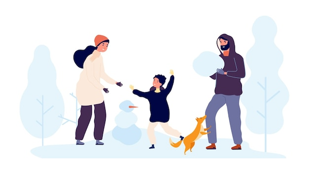 Activité de plein air d'hiver. famille construire des bonhommes de neige dans un parc enneigé.