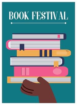 Affiche du festival du livre avec la main tenant la pile de livres